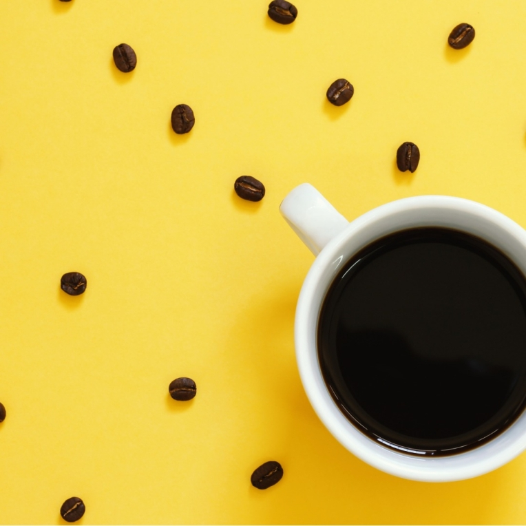 top-view-of-black-coffee-and-beans-on-yellow-background-picture-id626629272