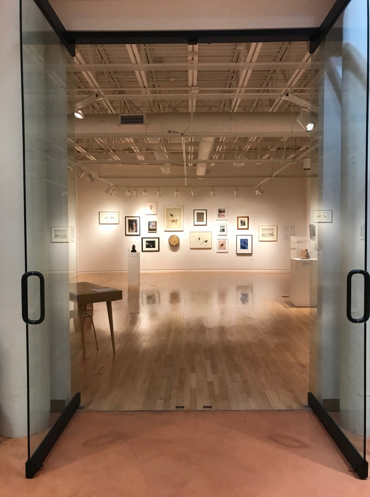 An image of the a gallery wall hung salon style with works of art