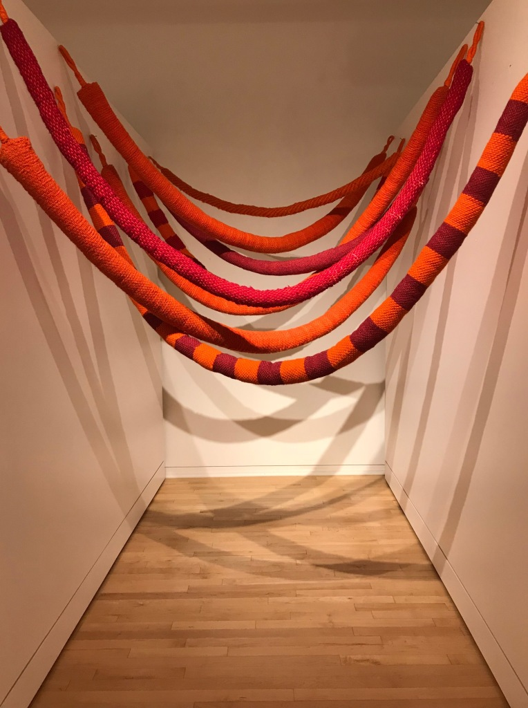 Tubular knitted sculptural rope-like forms, in red and orange, hanging in a gallery.